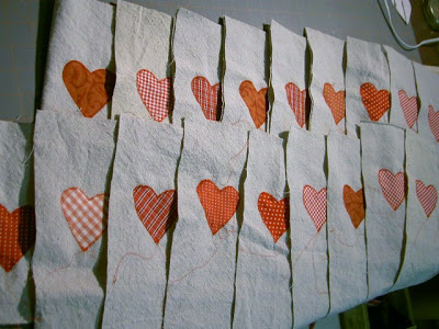 red cotton fabric heart appliqued onto drop cloth