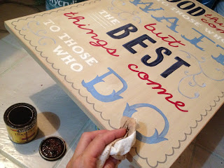 applying stain to handpainted wood sign to distress
