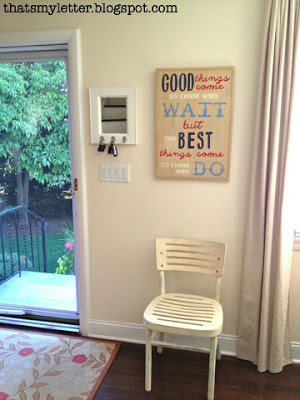 simple front door entry with chair, mirror and sign