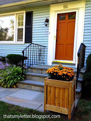 orange front door with wood planter