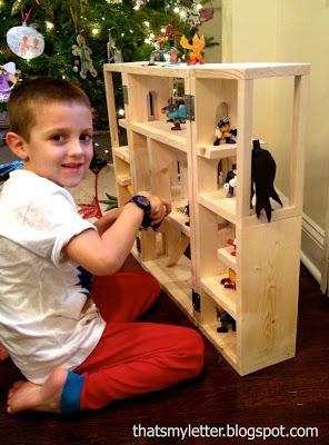 boy playing with superhero house