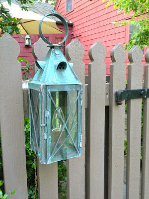 copper exterior sconce on fence