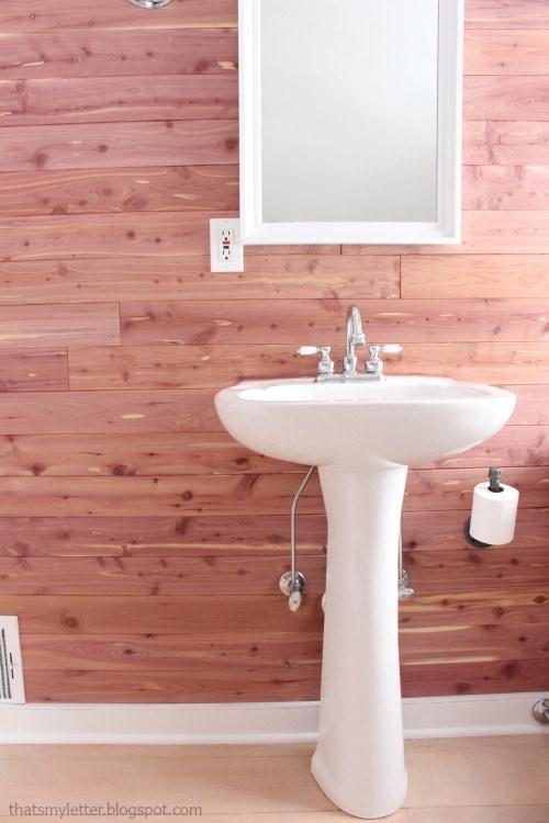 white pedestal sink cedar planked walls