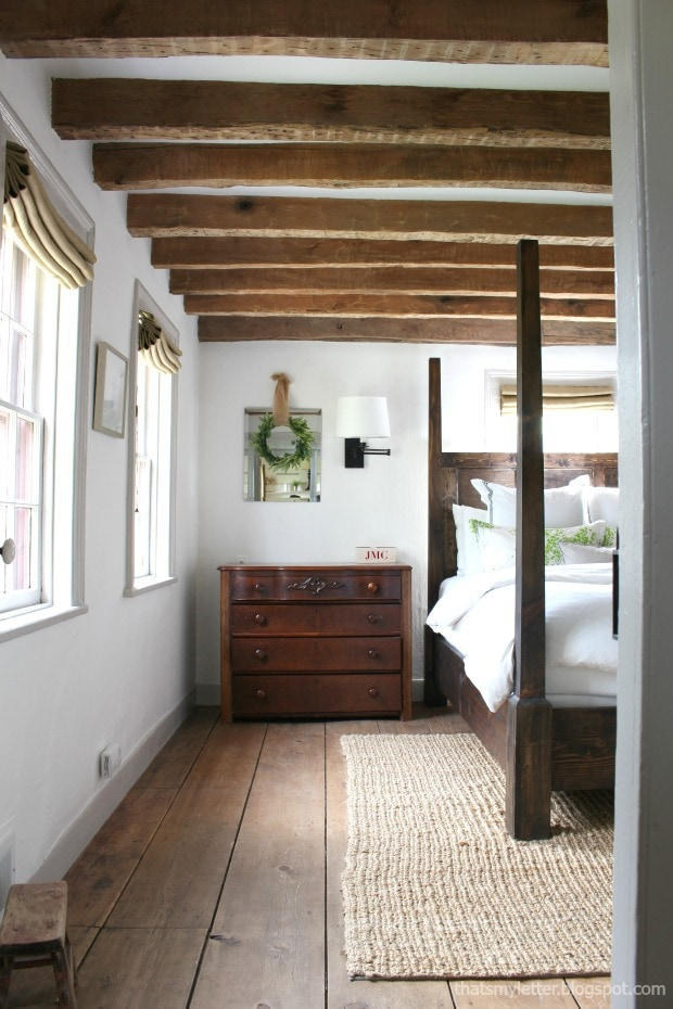 antique farmhouse master bedroom with original wood beams