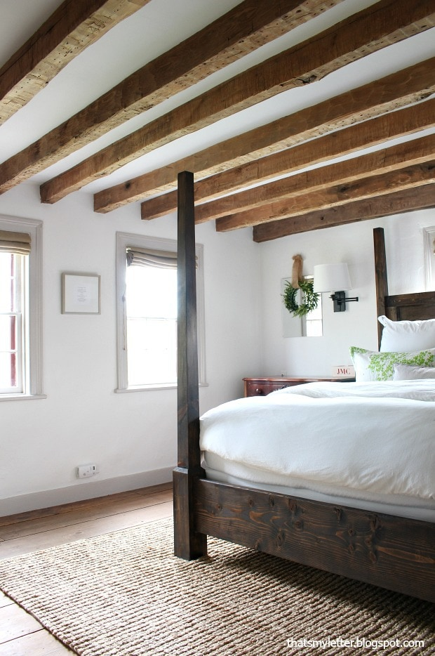 master bedroom in antique farmhouse wood beam ceiling