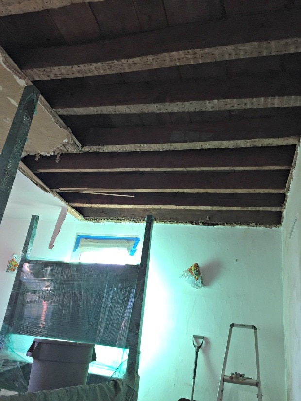 exposed wood beams with floor boards visible above