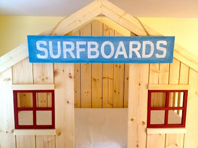 surfboards sign on clubhouse bed