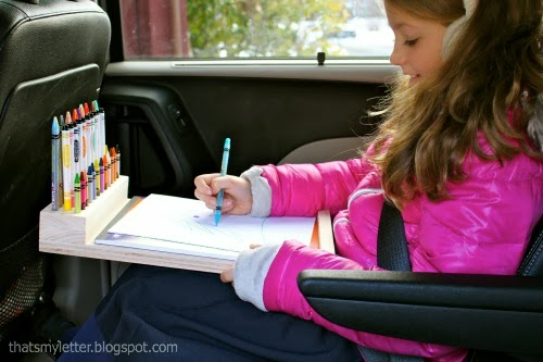young girl with lap desk in car