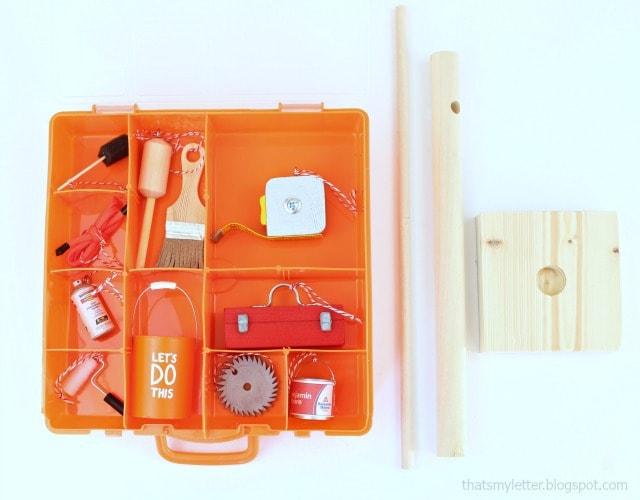 mini tool ornaments in plastic orange storage box with wood tree parts