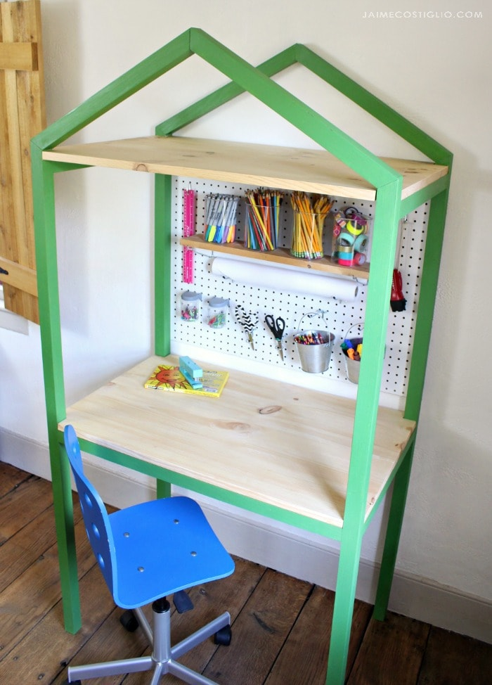 house shaped desk space with peg board