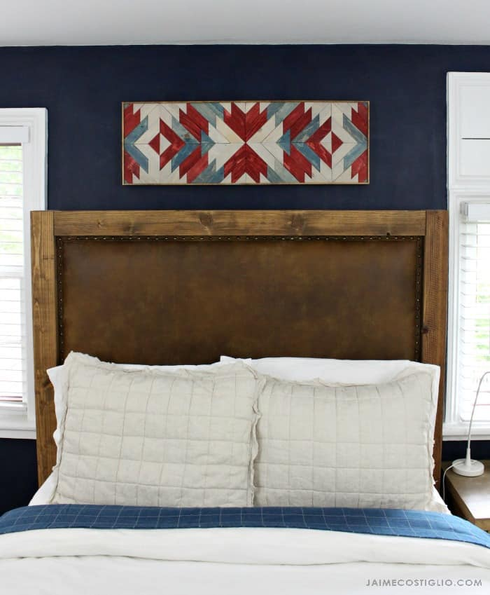 stained wall art above bed