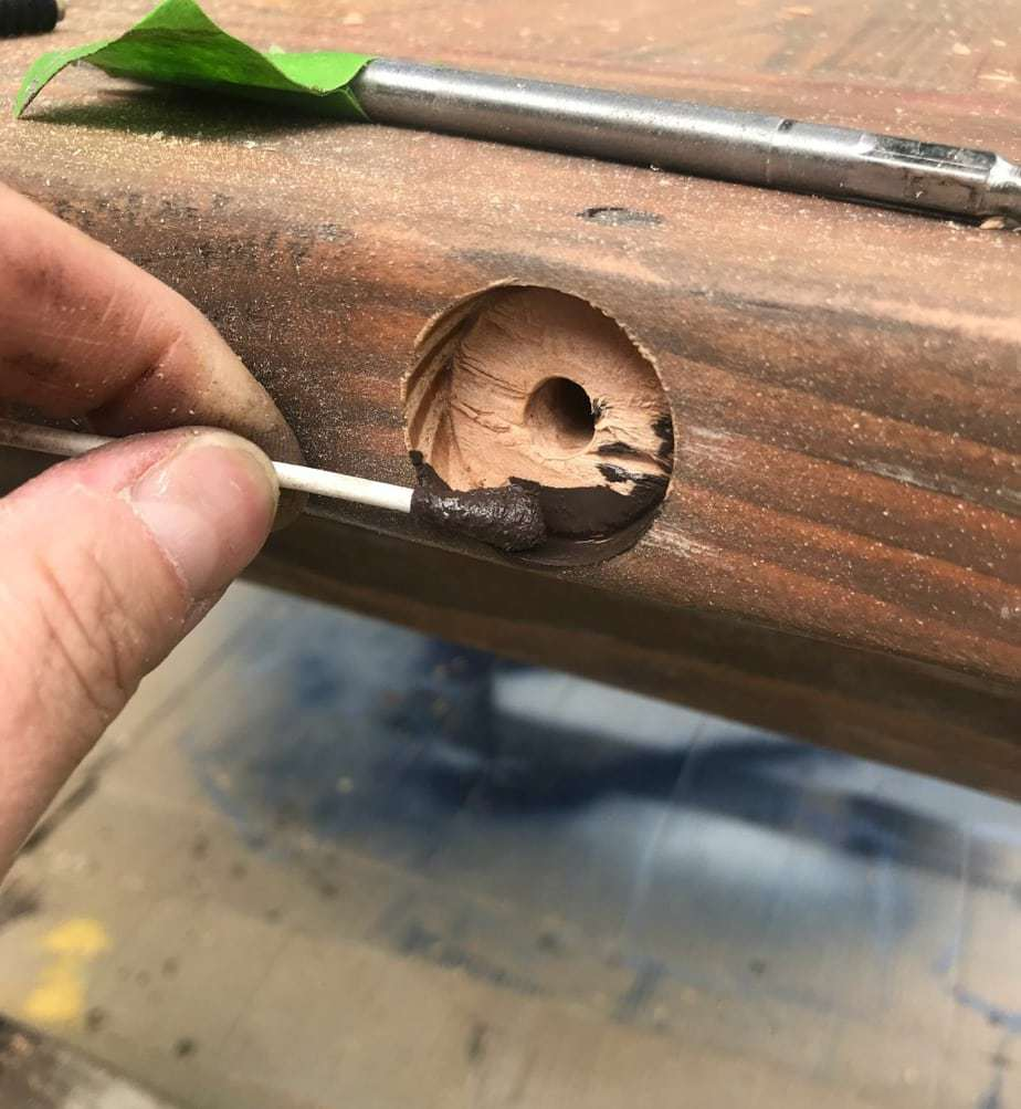 table breadboard hardware applying stain into hole