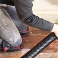 sanding wood floor wearing knee pads