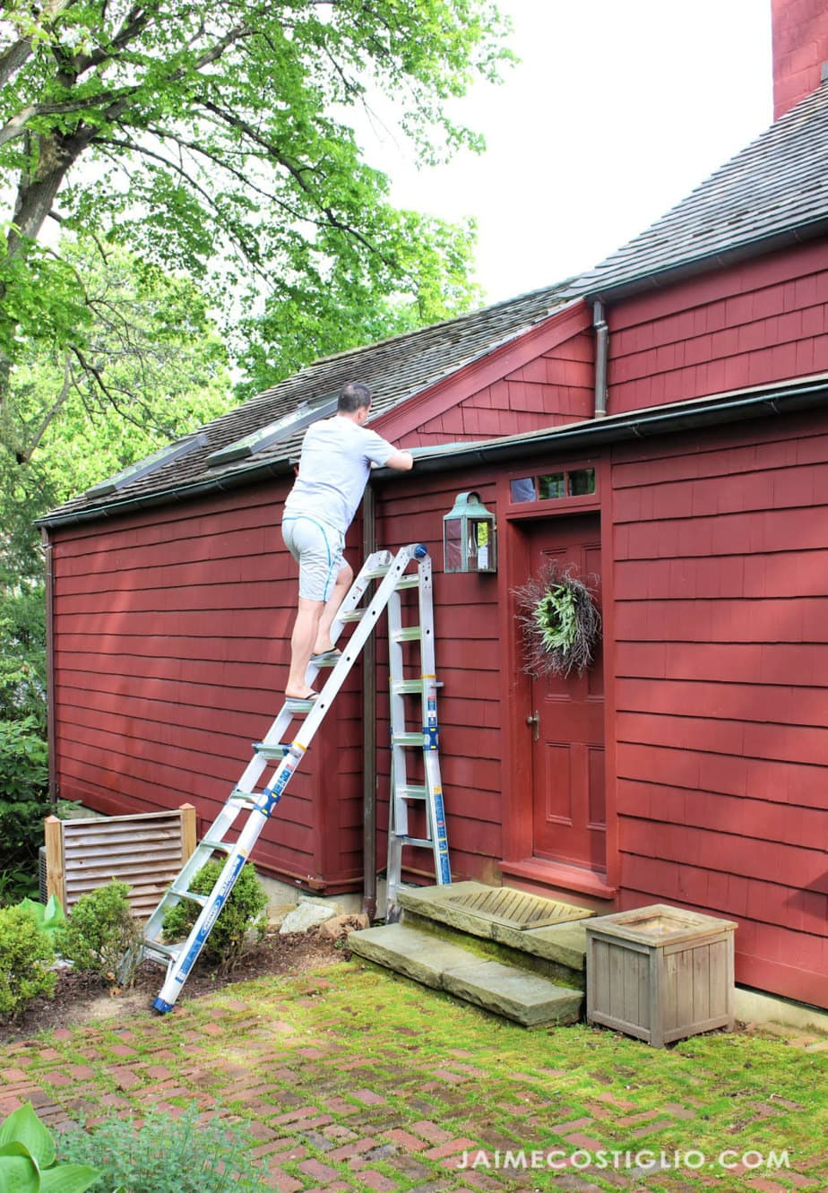 cleaning gutters with wall ladder