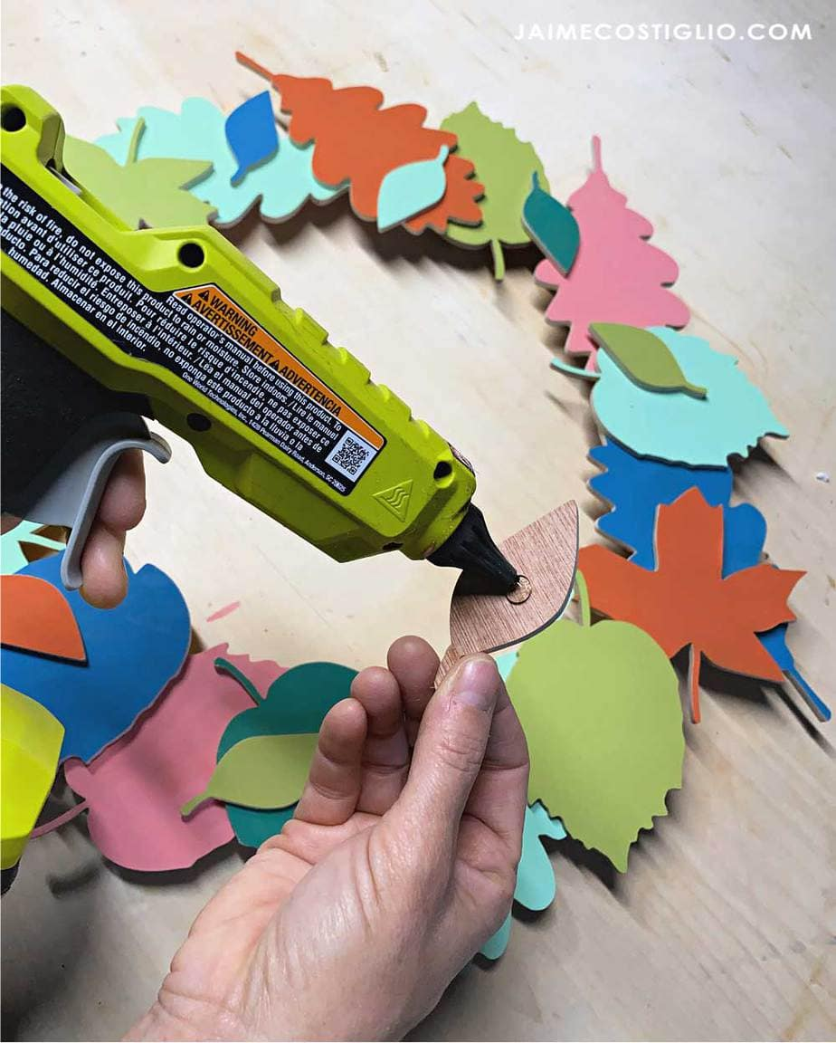 hot gluing wood leaves to wreath