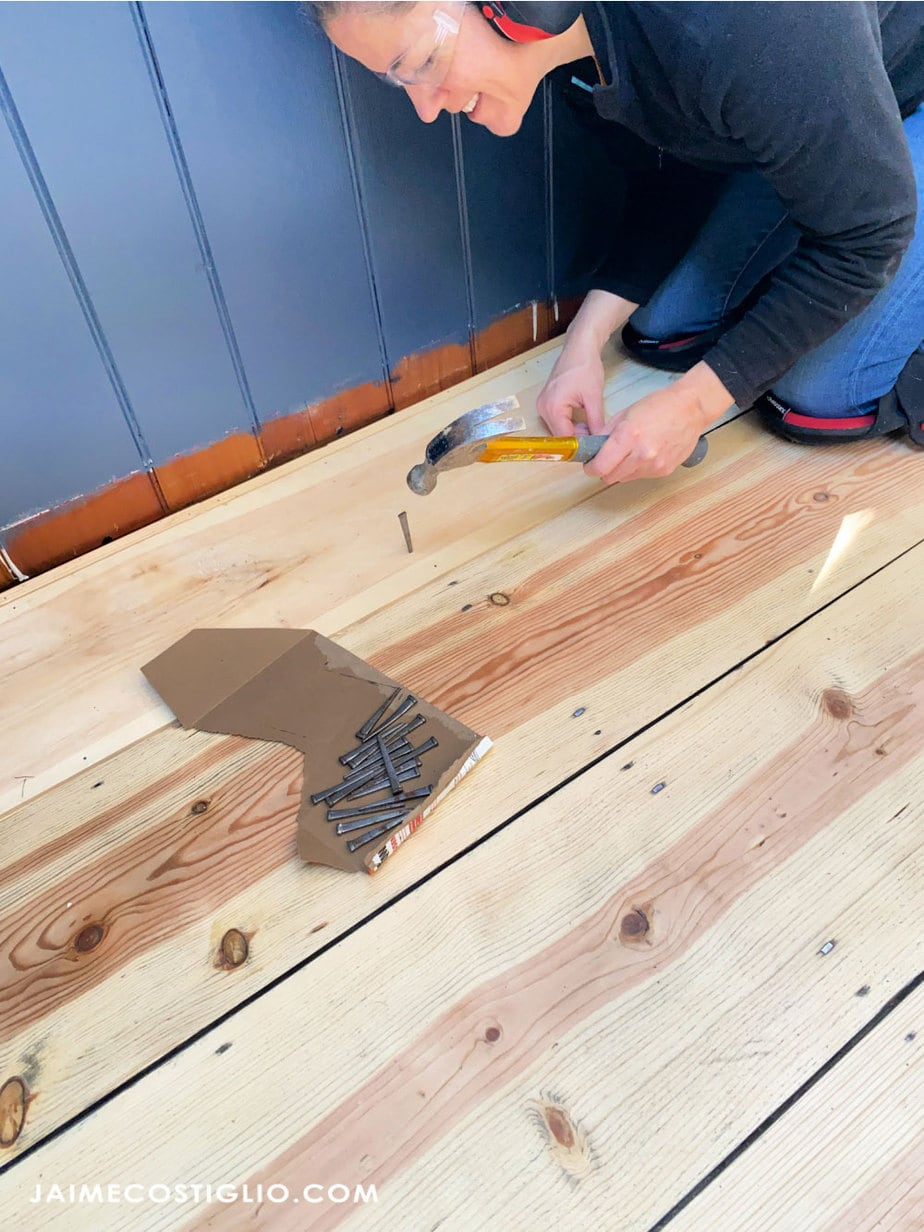 hammering in square cut nails into floor