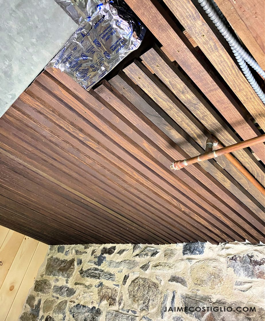 ceiling with visible vent and pipes